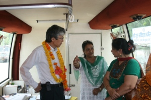 HE Mr. Yagi with members of the Asha Team inside one of the mobile health buses